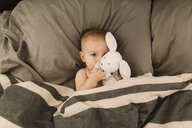 Portrait of baby girl lying in bed hugging toy rabbit, overhead view - CUF02783