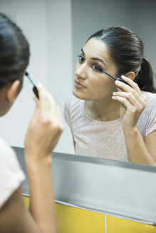 Woman applying mascara in front of mirror - CUF02789
