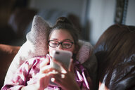 Girl relaxing on sofa, looking at smartphone - CUF02792