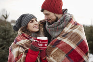 Romantic young couple wrapped in blanket while shopping for christmas tree from forest - CUF02921