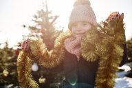 Girl in christmas tree forest wearing tinsel, portrait - CUF02924