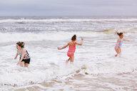 Three girls playing in ocean waves, Dauphin Island, Alabama, USA - CUF02963
