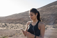 Young female runner looking at smartphone in arid  landscape, Las Palmas, Canary Islands, Spain - CUF02978