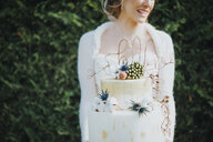 Bride with wedding cake, hedge in background - CUF02990