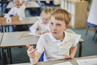 Schoolboy counting with fingers in classroom at primary school - CUF03065