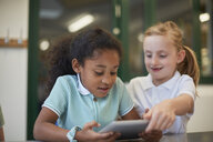 Two schoolgirls looking at digital tablet in classroom at primary school - CUF03080