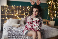 Young woman sitting on edge of bed, wearing christmas jumper and antlers, thoughtful expression - CUF03125