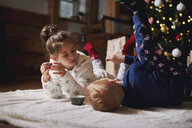 Young girl and boy relaxing beside Christmas tree - CUF03131