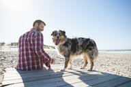 Man sitting on beach boardwalk with dog - CUF03161
