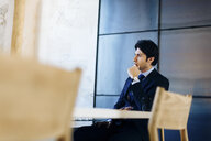 Businessman sitting at desk, thoughtful expression - CUF03239