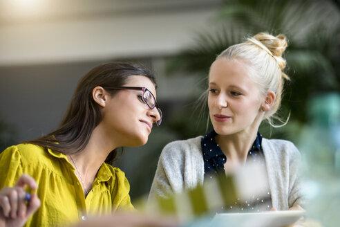 Two female designers meeting at design studio desk - CUF03272