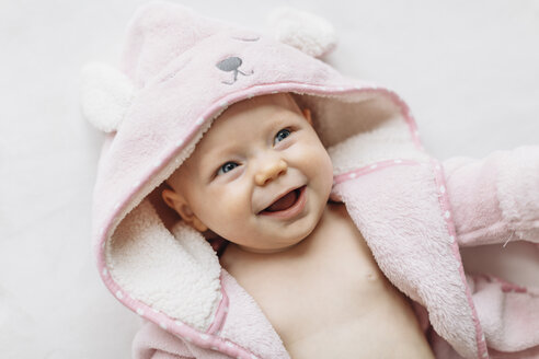 Portrait of baby girl in hooded towel looking away smiling - CUF03296