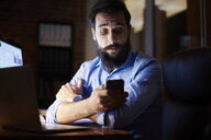 Young businessman looking at smartphone at office desk at night - CUF03308