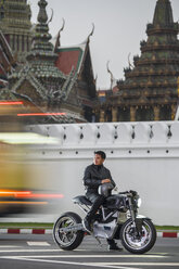 Man with electric motorbike by royal palace, Bangkok, Thailand - CUF03320