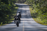 Rear view of motorcyclist riding on tree lined road, Khao Yai national park, Prachin Buri, Thailand - CUF03326