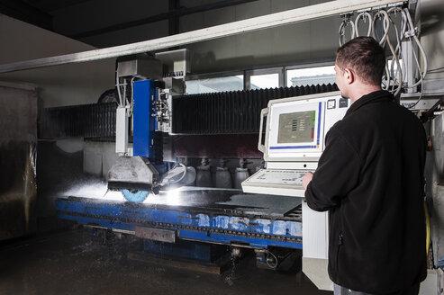 Stonemason working with CNC machine in his workshop - CVF00460