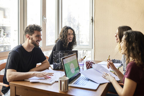 Four happy students at desk learning together - JRFF01619