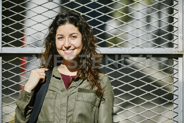 Portrait of smiling young woman at a fence - JRFF01628