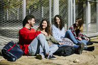 Four happy friends sitting at fence talking - JRFF01631