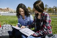 Two smiling female students sitting in park learning together - JRFF01634