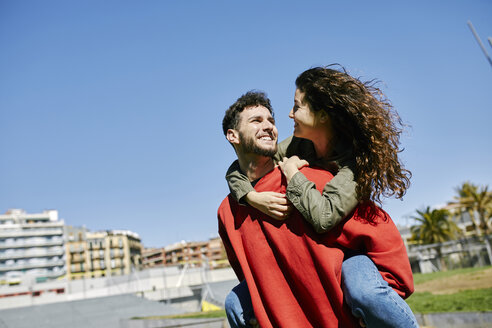 Happy young man giving girlfriend a piggyback ride - JRFF01637