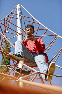 Young man using cell phone on a climbing frame on a playground - JRFF01640