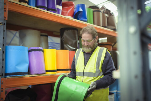 Worker selecting coloured vinyl rolls in factory - CUF03437
