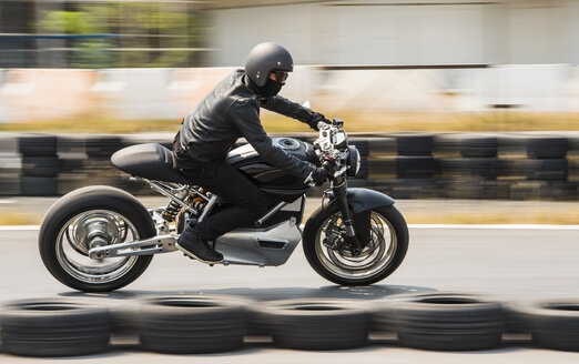 Man testing electric cafe racer motorbike on race track - CUF03440