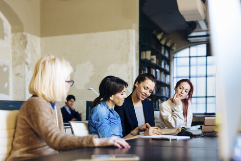 Four businesswomen sitting at desk in office, looking through book - CUF03458