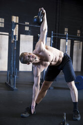 Man exercising in gymnasium, using kettlebell - CUF03488