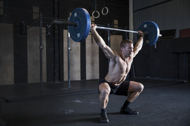 Man exercising in gym, using barbell, front squat position - CUF03533