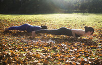 Two women doing yoga in park on autumn day - CUF03602