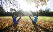 Two women doing yoga in park on autumn day - CUF03608