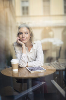 Mid adult woman with digital tablet in cafe window seat - CUF03626