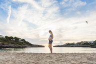 Pregnant woman standing on beach, looking at stomach - CUF03665