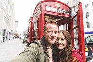 Couple taking selfie by telephone booth, London, UK - CUF03686