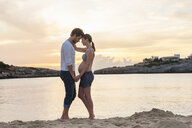 Pregnant woman and man, standing face to face on beach, holding hands - CUF03710