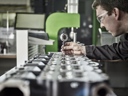 Worker in metalworking factory controlling cylinder head - CVF00467