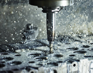 CNC machine drilling into cylinder head with coolant - CVF00470