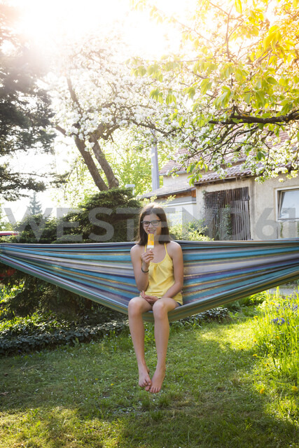 Smiling girl sitting on hammock in the garden eating ice lolly - LVF06960