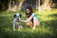 Girl feeding Dalmatian in the garden - LVF06967