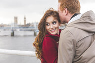 Couple hugging on bridge over the Thames, London, UK - CUF03726