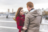 Couple hugging on bridge over the Thames, London, UK - CUF03735