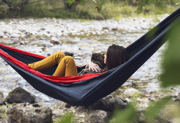 Young woman relaxing in hammock with dog, outdoors - CUF03813