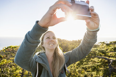 Female hiker taking selfie in coastal forest, Pacific Rim National Park, Vancouver Island, British Columbia, Canada - CUF03855