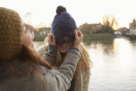 Young woman putting knitted hat on friend, hat covering eyes, laughing - CUF03936