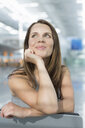 Portrait of businesswoman looking up in airport departure lounge - CUF03966