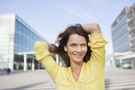 Portrait of businesswoman with hands behind head at airport - CUF03969