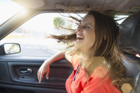 Mid adult woman with flyaway hair in front seat of car - CUF04017