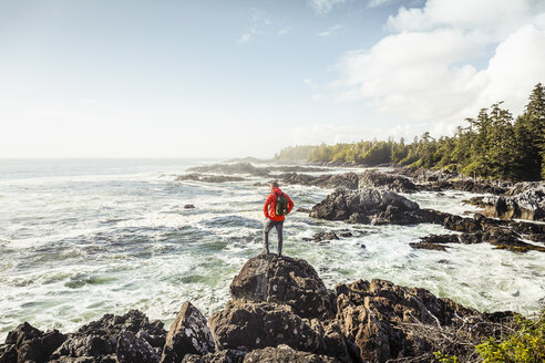 Male hiker looking out to sea from rocky coast, Wild Pacific Trail, Vancouver Island, British Columbia, Canada - CUF04095